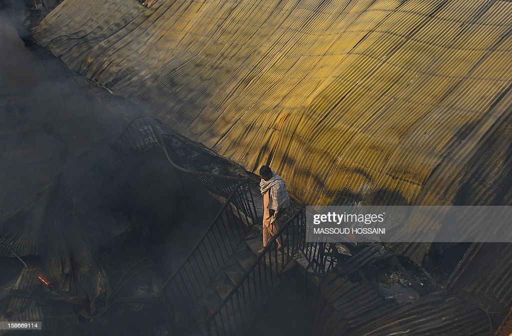 An Afghan man walks through the area of a fire that swept through a market in Kabul on December 23, 2012. A huge fire swept through a market in downtown Kabul on December 23, destroying hundreds of shops and forcing the city's nearby money exchange to evacuate, police and witnesses said. There were no reports of any casualties in the early morning blaze which destroyed most of the cloth market's 500 shops, Kabul fire department officials told AFP. AFP PHOTO/ Massoud HOSSAINI