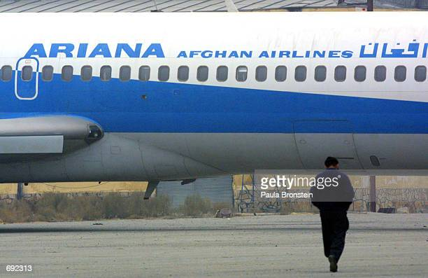 An Afghan man walks towrds an Ariana Afghan Airlines plane on the tarmac at the Kabul airport January 10 2002 in Kabul Afghanistan The airport is in...