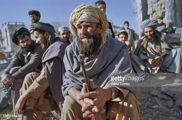 An Afghan man wearing a lungee turban and patoo shawl, the barrel of his rifle held between his hands, with similarly dressed men in the background,...