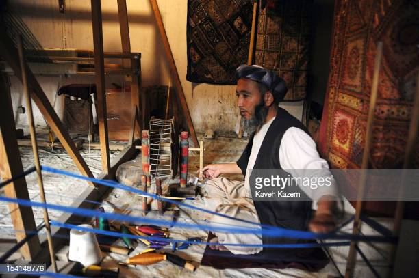 An Afghan man weaves silk head scarves and shawls with an oldfashioned wooden weaving machine on a top floor of a handicraft shop in Chicken Street...
