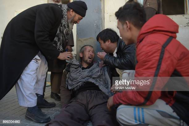 TOPSHOT An Afghan man weeps for his relatives at a hospital following explosions at a Shiite cultural centre in Kabul on December 28 2017 At least 40...