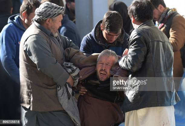 An Afghan man weeps for his relatives at a hospital following blasts at a Shiite cultural centre in Kabul on December 28 2017 At least 40 people were...