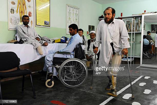 An Afghan man who lost his left leg on a land mine walks at an International Committee of the Red Cross hospital for war victims and the disabled in...