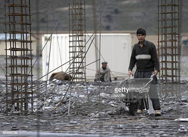 An Afghan man works on a construction site at ISAF's Camp Bostick in Naray, in the eastern Kunar province on April 15, 2009. United States President...