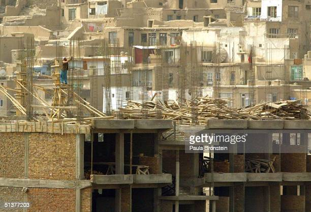An Afghan man works on a construction site that will become a marketplace September 30 2004 in downtown Kabul Afghanistan Kabul is rebuilding after...