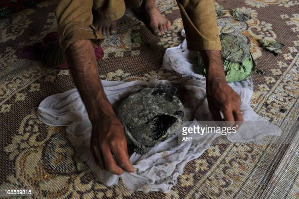 An Afghan man wraps a package of opium after harvesting from his poppy field in Pachir district of Nangarhar province on May 11 2013 The United...