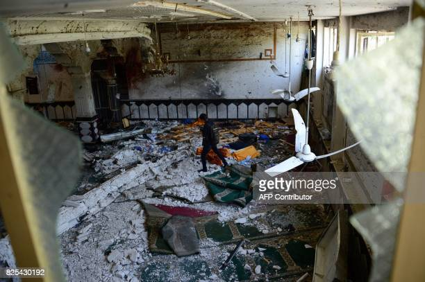 TOPSHOT An Afghan media personnel walks through a Shiite mosque after it was attacked by suicide bombers in Herat on August 2 2017 Thirty worshippers...