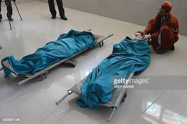 An Afghan medical worker looks at the bodies of two foreign women who were gunned down by men on a motorcycle at the morgue of Herat hospital on July...
