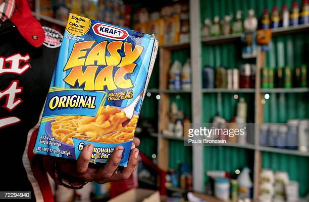 An Afghan merchant holds a box of Kraft Easy Mac Macaroni and Cheese Dinner at the Bush Bazaar October 29 2006 in Kabul Afghanistan The small black...
