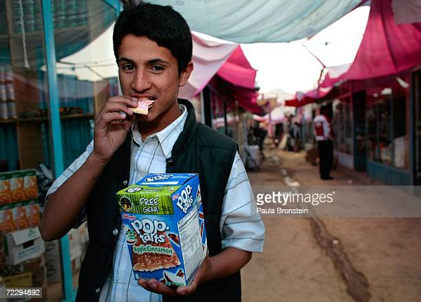 An Afghan merchant takes a bite of a PopTart outside his shop at the Bush Bazaar October 29 2006 in Kabul Afghanistan The small black market named...