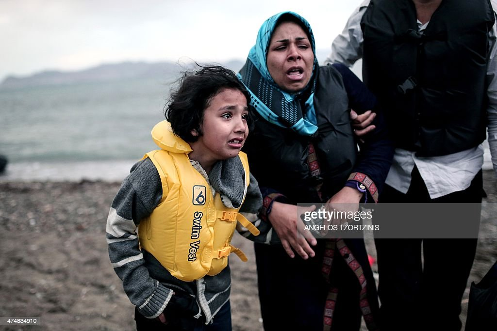 An Afghan migrant girl holds the hand of a woman as they arrive on a beach on the Greek island of Kos, after crossing a part of the Aegean Sea between Turkey and Greece, on May 27, 2015. / AFP / ANGELOS