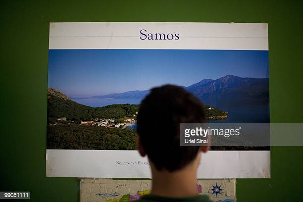 An Afghan migrant looks at a poster of the island of Samos on the wall of his room in an institute for underage migrants on May 3 2010 in Agiasos...