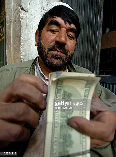 An Afghan money changer counts US dollars at the money exchange market in Kabul 31 December 2007The Afghani currently stands at 4970 against the USD...