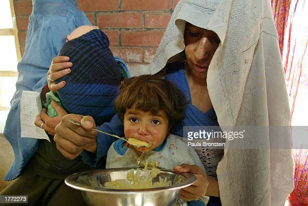 An Afghan mother feeds her baby porridge at the Action Contre La Faim Supplemental Feeding Center February 9 2003 in Anawba Panjchir Valley...
