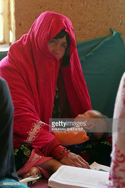 An Afghan mother holds her sleeping child while attending a literacy class in Bamiyan province on May 31, 2014. Some 60 literacy training centres,...