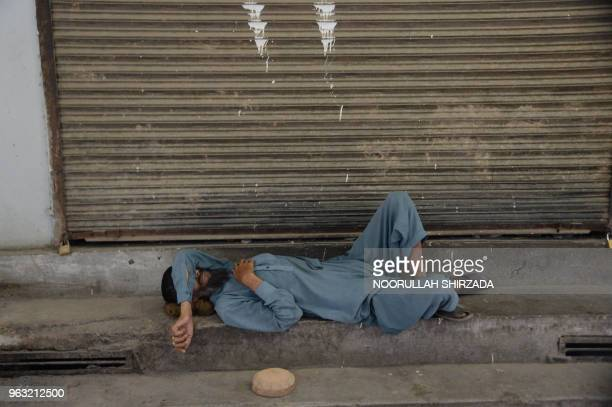 An Afghan Muslim man sleep in front of a shop during the Islamic holy month of Ramadan in Jalalabad on May 28, 2018. - Muslims throughout the world...