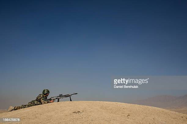 An Afghan National Army cadet takes cover on the edge of a hill as he prepaes to offer cover with his M-40 machine gun, armed with blanks, during a...