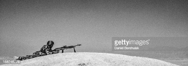 An Afghan National Army cadet takes cover on the edge of a hill as he prepares to offer cover with his M-40 machine gun, armed with blanks, during a...
