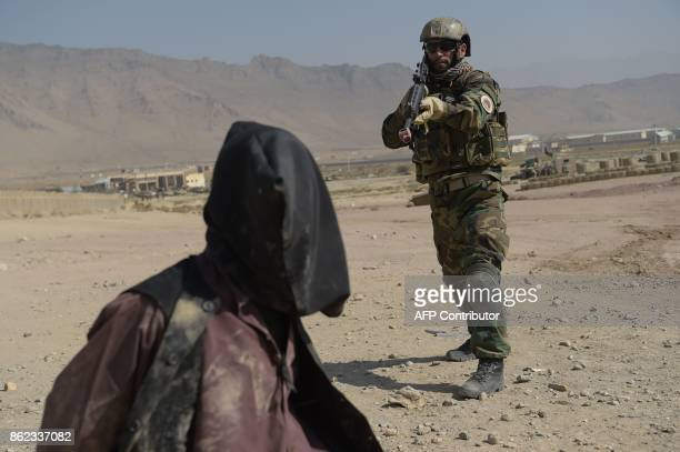 An Afghan National Army commando arrests a man pretending to be a Taliban fighter during a military exercise at the Kabul Military Training Centre on...