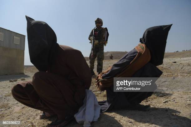 An Afghan National Army commando arrests men pretending to be Taliban fighters during a military exercise at the Kabul Military Training Centre on...