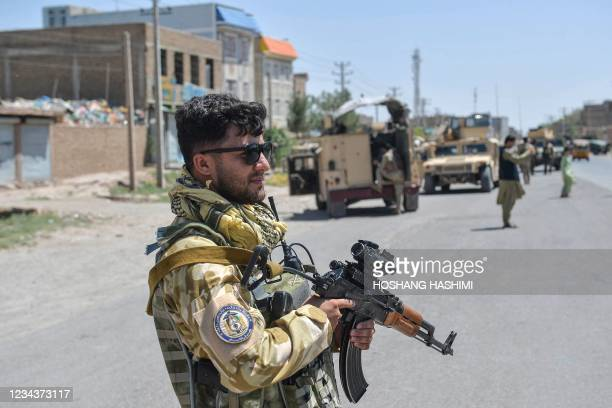 An Afghan National Army commando stands guard along the road in Enjil district of Herat province on August 1 as skirmishes between Afghan National...