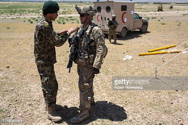 An Afghan National Army officer left speaks with a US Army soldier from the 4th Brigade 3rd Infantry Division May 6 2013 while setting up an Afghan...