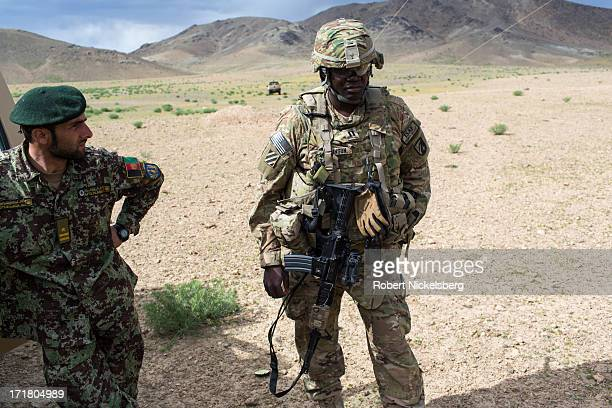 An Afghan National Army officer, left, stands with a U.S. Army officer from the 4th Brigade, 3rd Infantry Division, center, May 6, 2013 during a...