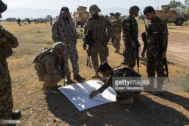 An Afghan National Army officer, lower right, shows his U.S. Army counterparts from the 4th Brigade, 3rd Infantry Division, left and center, about...