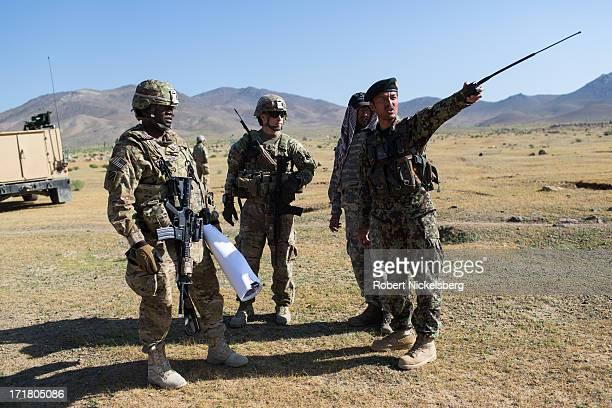 An Afghan National Army officer, right, informs his U.S. Army counterparts from the 4th Brigade, 3rd Infantry Division, left and center, about ANA...