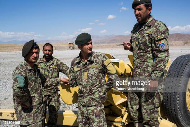 An Afghan National Army officer, right, shows a group of Afghan soldiers how to fire an artillery gun May 5, 2013 at Forward Operating Base Shank,...