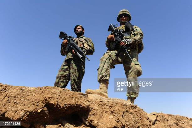 An Afghan National Army soldier and a member of the NATOled International Security Assistance Force stand guard during a graduation ceremony at the...