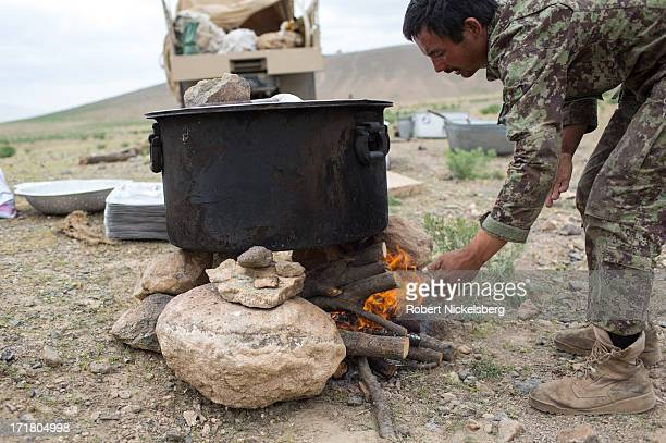 An Afghan National Army soldier from the 7th Kandak adds wood to a fire May 6, 2013 during a joint operation with U.S. Army soldiers in Babus,...