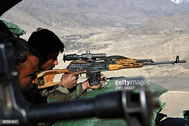 An Afghan National Army soldier from the OMLT of the Kandak 32 aims his Dragunov sniper rifle from an 'Eagle's Nest' observation post in the Alah Say...