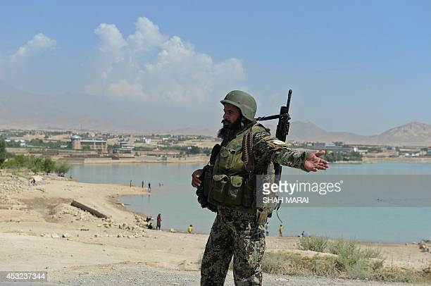 An Afghan National Army soldier gestures to stop a vehicle at a checkpoint near the Marshal Fahim National Defense University on the outskirts of...