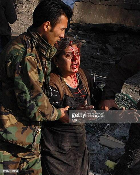 An Afghan National Army soldier helps a wounded woman at the site of a suicide attack near a guest house in Kabul on December 15 2009 A suspected...