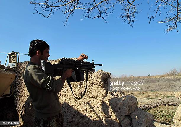 An Afghan National Army soldier keeps watch during an ongoing battle with Taliban militants in the Nad Ali district of Helmand on December 22 2015...