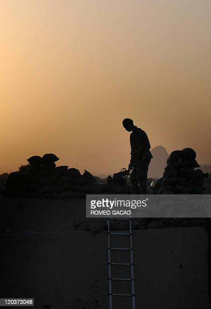 An Afghan National Army soldier mans a checkpoint tower with US soldiers from the 1st Platoon Charlie Company 287 Infantry 3d Brigade Combat Team...