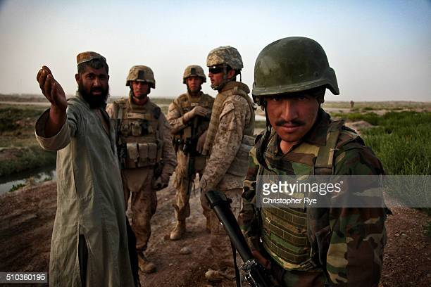 An Afghan National Army Soldier posts security as Captain Chad Althiser India Battery Commander 3rd Battalion 11th Marines speaks with an Afghan...