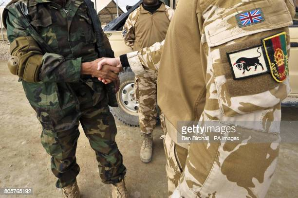 An Afghan National Army soldier shakes hands with a British Forces soldier at Camp Bastion as they prepare to carry out a Combat Logistics Patrol...
