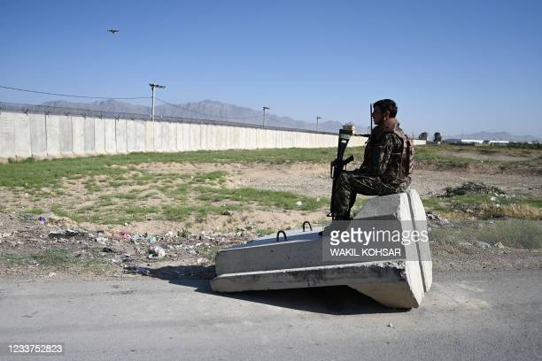 An Afghan National Army soldier sits at a road checkpoint near the a US military base in Bagram, some 50 km north of Kabul on July 1, 2021.