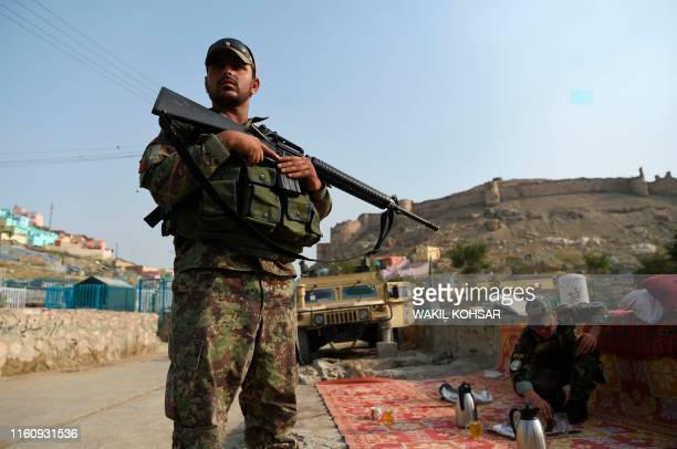 An Afghan National Army soldier stands during the Eid al-Adha festival near the old fortress of Bala Hissar in Kabul on August 11, 2019. - Afghans...