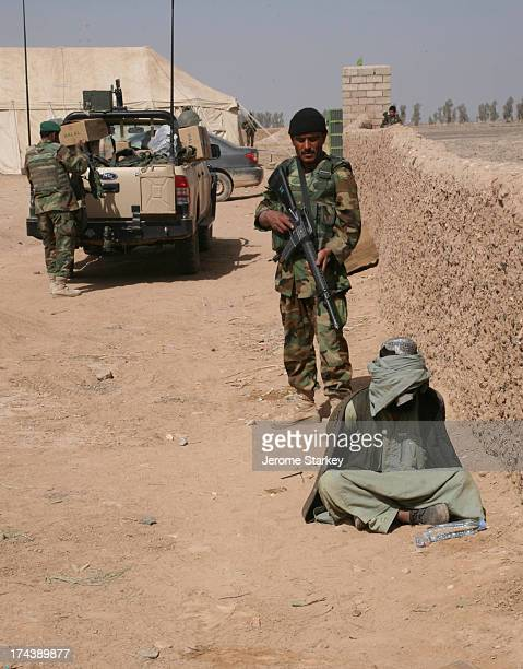 CONTENT] An Afghan National Army soldier stands guard as a suspected Taliban militant sits blindfolded and hands tied on the ground inside a...