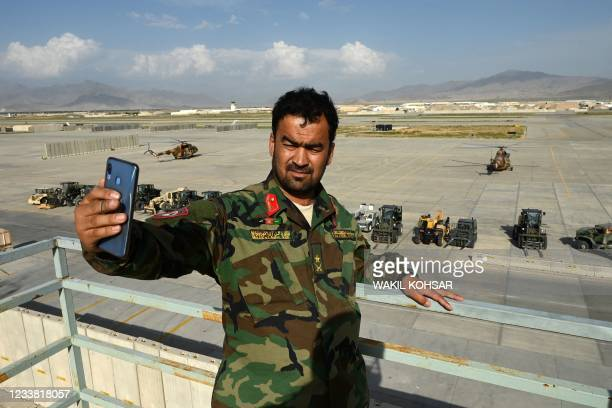 An Afghan National Army soldier takes a selfie with his mobile phone inside the Bagram US air base after all US and NATO troops left, some 70 Kms...