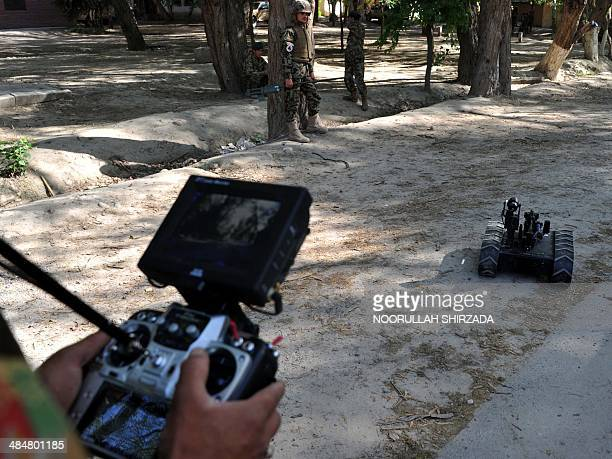 An Afghan National Army soldier uses a robotic device during an IED defusing training exercise in Jalalabad, Nangarhar province on April 14, 2014....