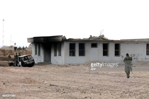An Afghan National Army soldier walks at the scene of a suicide attack outside a base in Zhari district Kandahar province on January 20 2014 Nine...