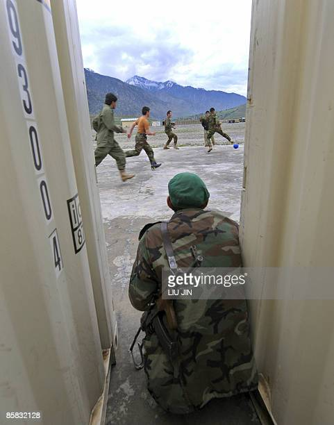 An Afghan National Army soldier watches his fellow soldiers playing football at the ISAF's Camp Bostick in Naray, in Afghanistan's eastern Kunar...