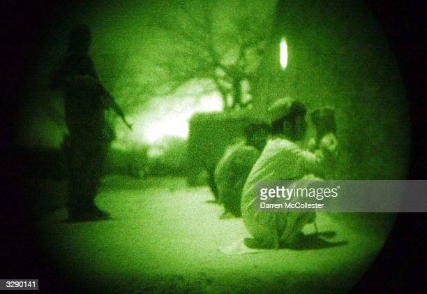 An Afghan National Army soldier watches over detainees March 29 2004 during a night mission conducted jointly with the US Special Forces in Shahak...