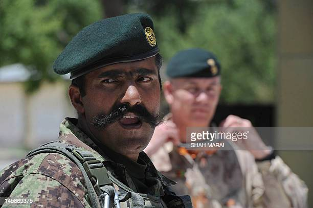 An Afghan National Army soldier with a US soldier keep watch during a joint press conference by Afghan Minister of Defence Abdul Rahim Wardak and US...