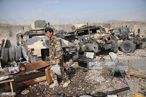 An Afghan National Army soldier works alongside heavily damaged Humvees in the motor pool at Forward Operating Base Maiwand, an ANA base that adjoins...