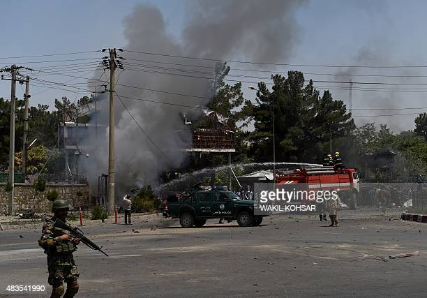 An Afghan National Army solider stands guard as firefighters spray water at the site of a bomb attack near the entrance to Kabul's international...